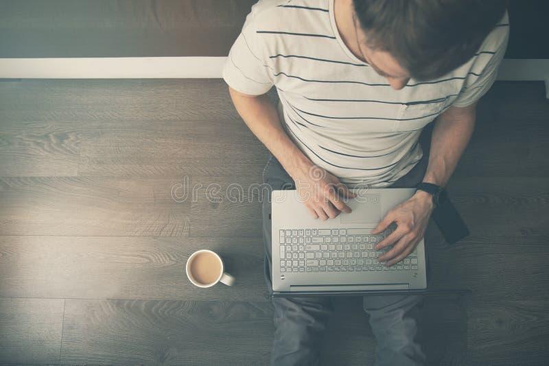 Trabalho da casa - homem que senta-se no assoalho e que usa o laptop imagens de stock royalty free