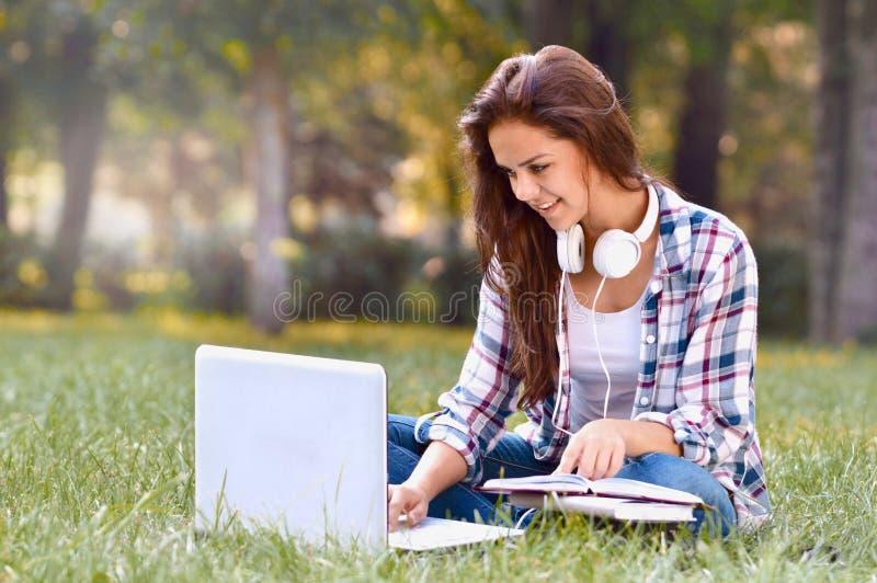Trabalho da menina do estudante no portátil que senta-se na grama no parque foto de stock