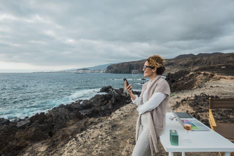 Trabalho da mulher de negócio exterior na liberdade total na frente do oceano com um desktop e um caderno e um telefone celular - fotografia de stock royalty free