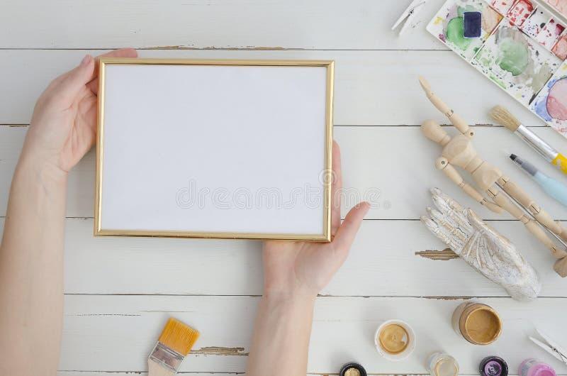 Trabalho de arte trocista acima Quadro da foto do ouro com mãos do artista da mulher Espaço para o texto, desenho, rotulação Conf foto de stock royalty free