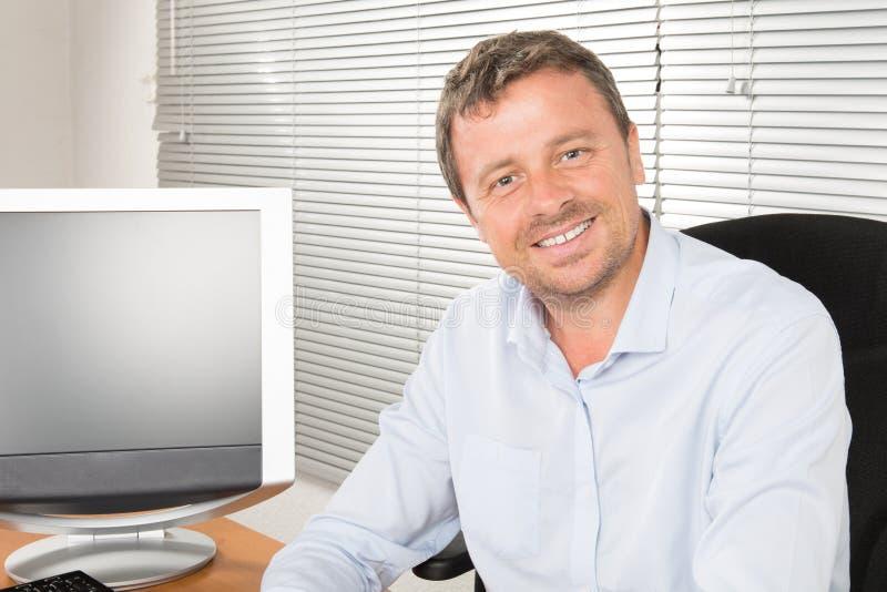 trabalho de assento do homem de negócios considerável com o portátil que olha a câmera e sorriso feliz no fundo do escritório fotos de stock royalty free