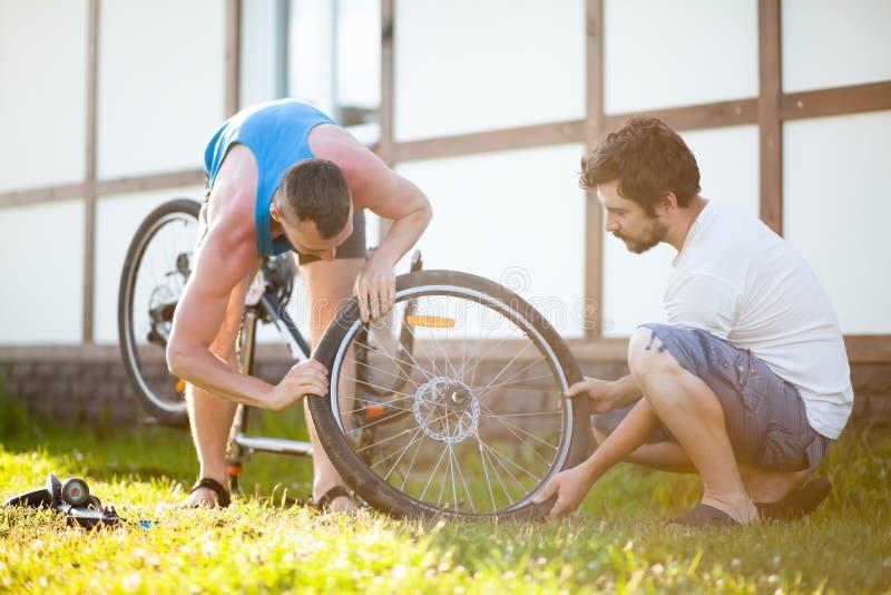 Trabalho de dois ciclistas que repara junto a bicicleta, reparo da bicicleta exterior foto de stock