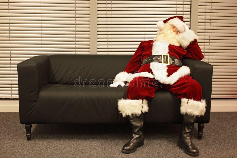Trabalho de espera do Natal, Papai Noel que dorme no sofá fotos de stock royalty free