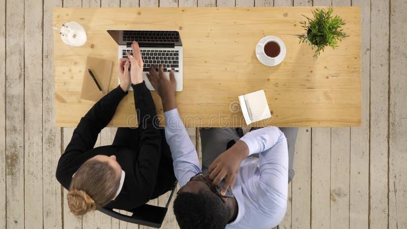Trabalho de Making Call Team do homem de negócios de Using Laptop And da mulher de negócios imagem de stock