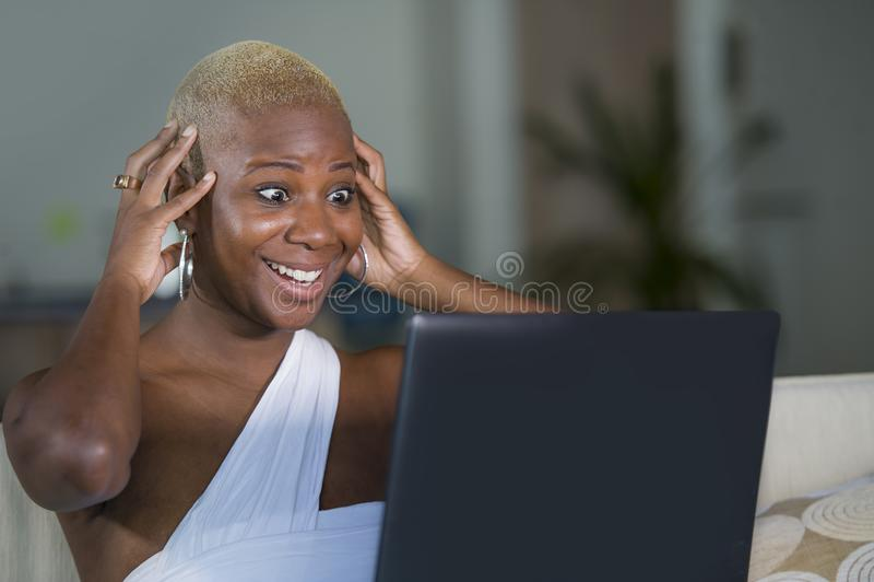 Trabalho de sorriso da mulher afro-americana preta feliz bonita nova no laptop em casa relaxado no sofá do sofá no onlin do Inter fotografia de stock