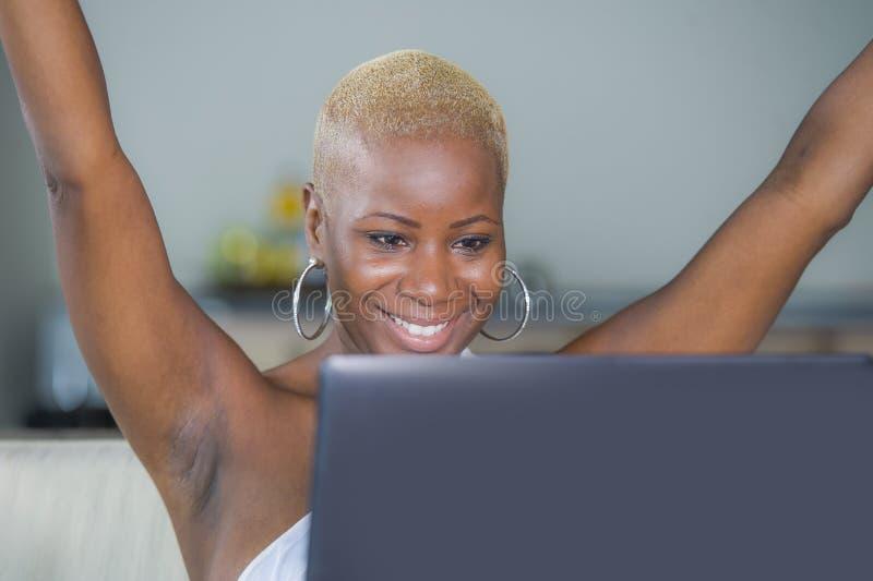 Trabalho de sorriso da mulher afro-americana preta feliz bonita nova no laptop em casa relaxado no sofá do sofá que comemora o su imagem de stock royalty free