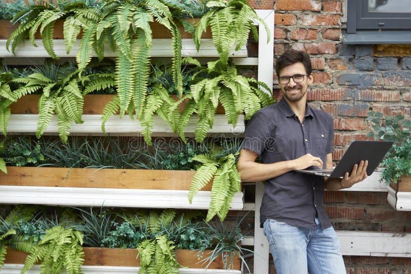 Trabalho de sorriso do empresário novo usando o portátil moderno Parede de tijolo próxima ereta, plantas, escritório do eco Execu foto de stock royalty free