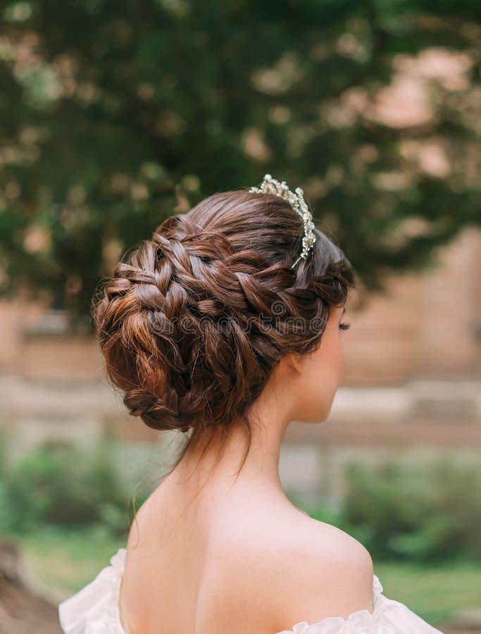 Trabalho de surpresa do cabeleireiro profissional, penteado delicado do cabelo marrom escuro longo e tiara para o baile de finali fotografia de stock royalty free
