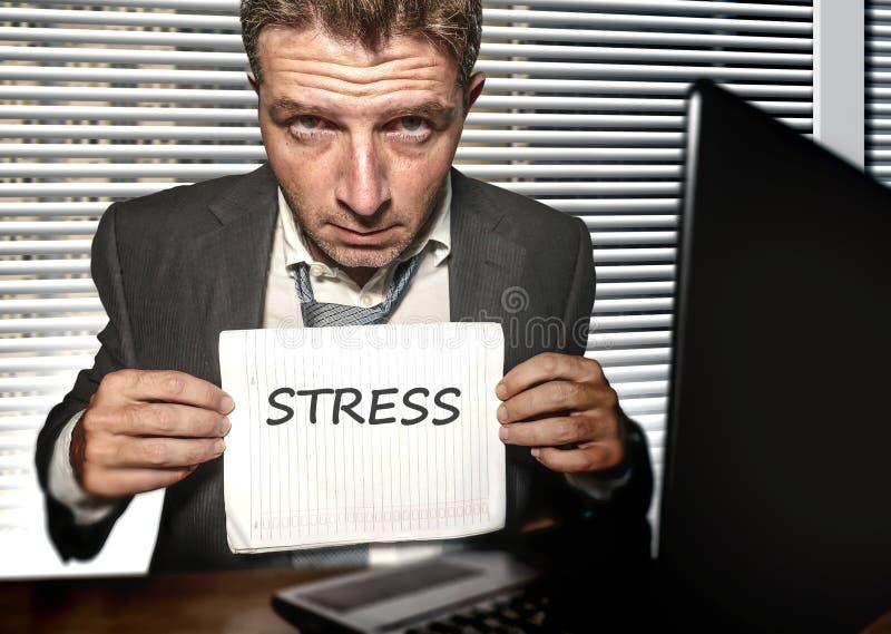 Trabalho desesperado e forçado novo do homem de negócio oprimido na mesa do computador de escritório que sente terra arrendada in imagens de stock royalty free