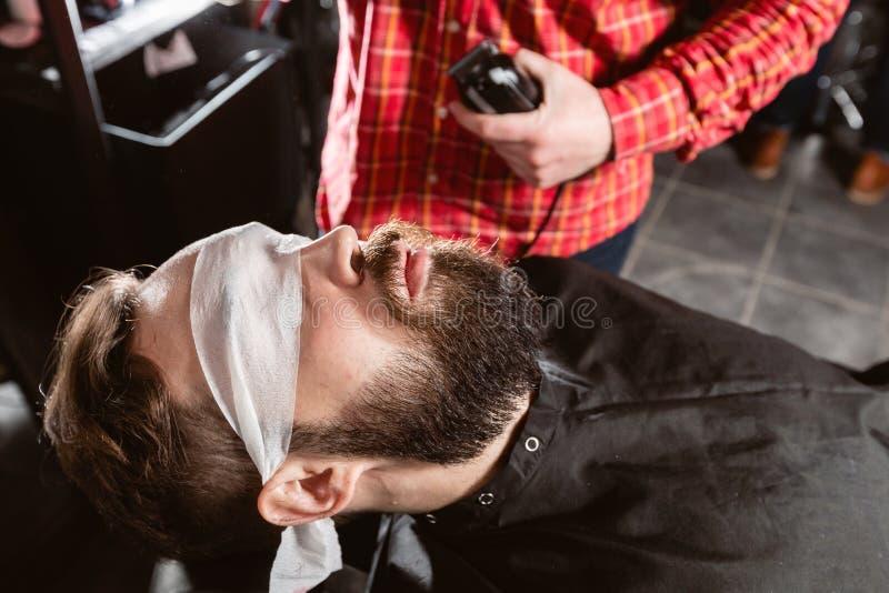 Trabalho do barbeiro com a máquina da tosquiadeira no barbeiro A ferramenta profissional do ajustador corta a barba e o cabelo d imagem de stock