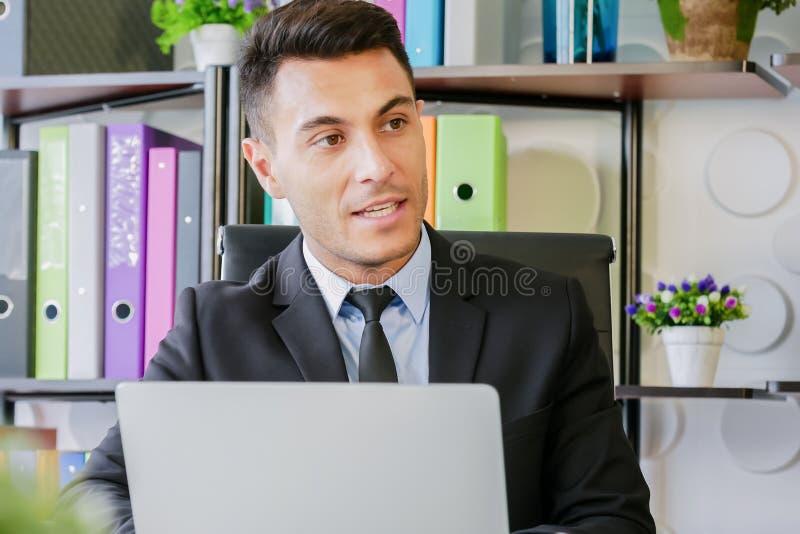 Trabalho do homem de negócio do retrato no escritório moderno que fala com laptop e que fala a alguém imagens de stock