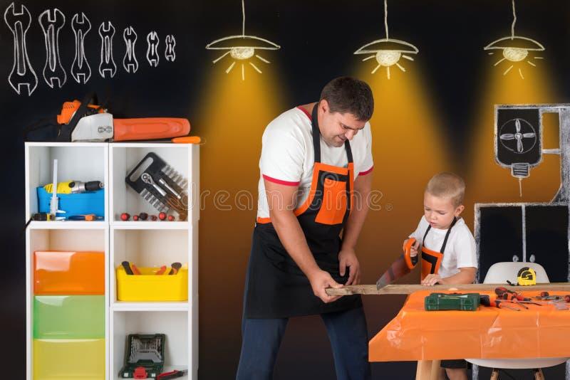 Trabalho do paizinho e do filho junto na loja da carpintaria O pai ensina seu filho cortar pranchas de madeira fotos de stock royalty free