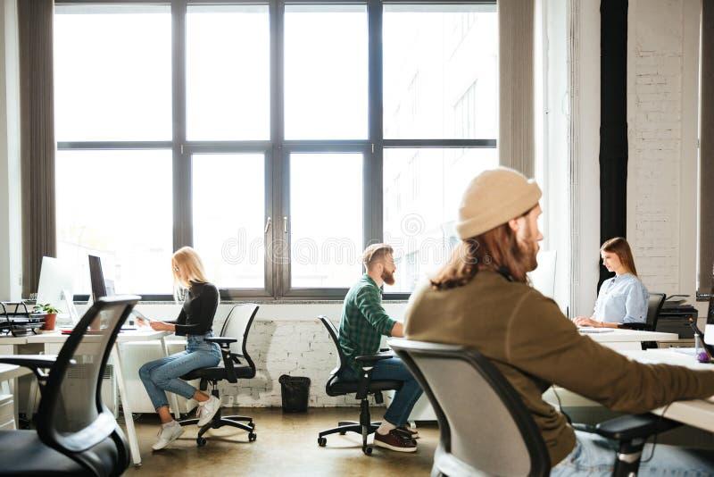 Trabalho dos colegas no escritório usando computadores Vista de lado fotografia de stock royalty free