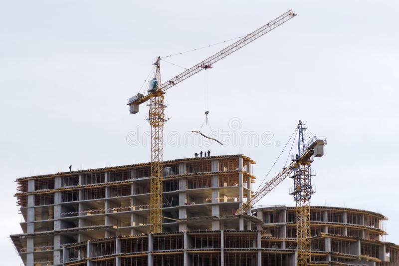 Trabalho dos construtores e do guindaste na construção da construção alta da elevação fotografia de stock