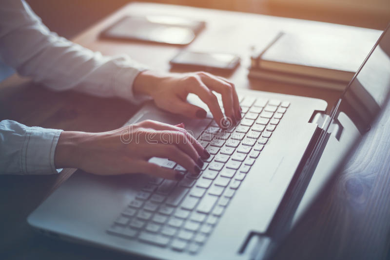 Trabalho em casa com a mulher do portátil que escreve um blogue Mãos fêmeas no teclado