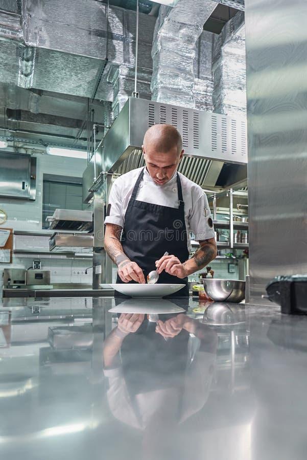 Trabalho em um restaurante Retrato vertical do cozinheiro chefe masculino profissional com tatuagens em seus braços que decora se imagens de stock royalty free