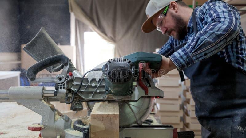 Trabalho experiente do carpinteiro com serra circular imagens de stock
