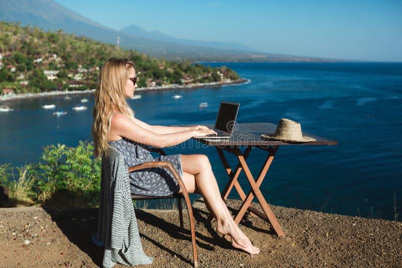 Trabalho fêmea com seu portátil perto do mar