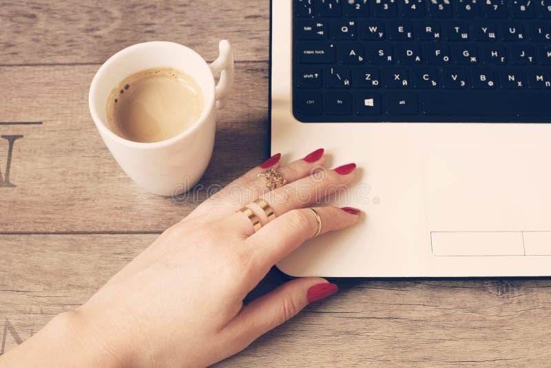 Trabalho fêmea no portátil em um café Caneca branca de café Feche acima de uma mão da mulher com anéis e os pregos longos, pintad foto de stock