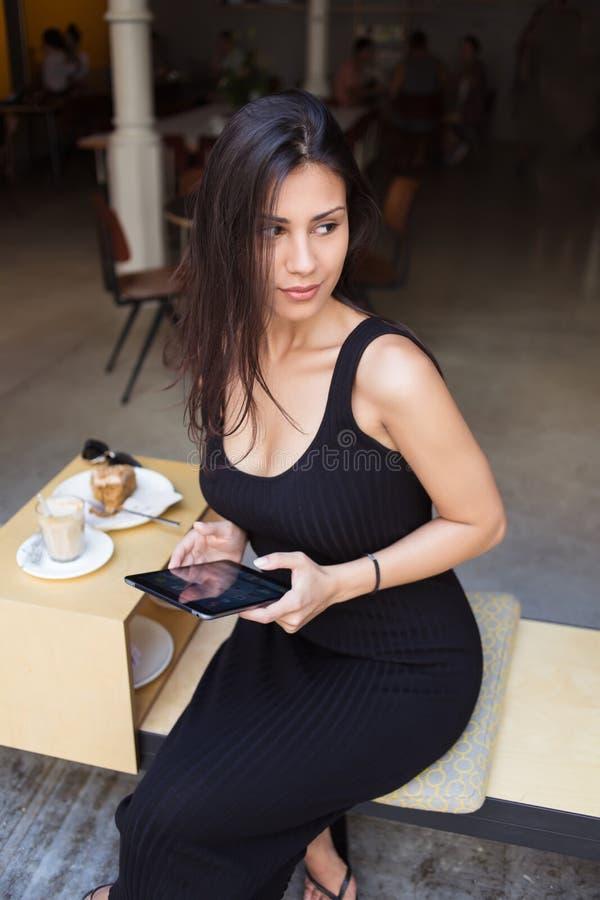Trabalho fêmea 'sexy' novo em sua almofada de toque durante a pausa para o almoço ao sentar-se no restaurante fora fotografia de stock royalty free