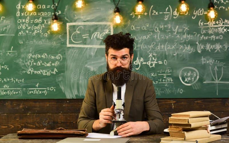 Trabalho farpado do homem com microscópio Homem com barba e bigode na escola O cientista faz a pesquisa sobre o quadro foto de stock royalty free