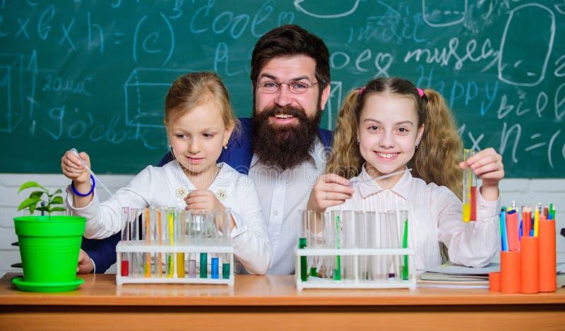 Trabalho farpado do professor do homem com microsc?pio e tubos de ensaio na sala de aula da biologia Experi?ncia da biologia da e foto de stock royalty free