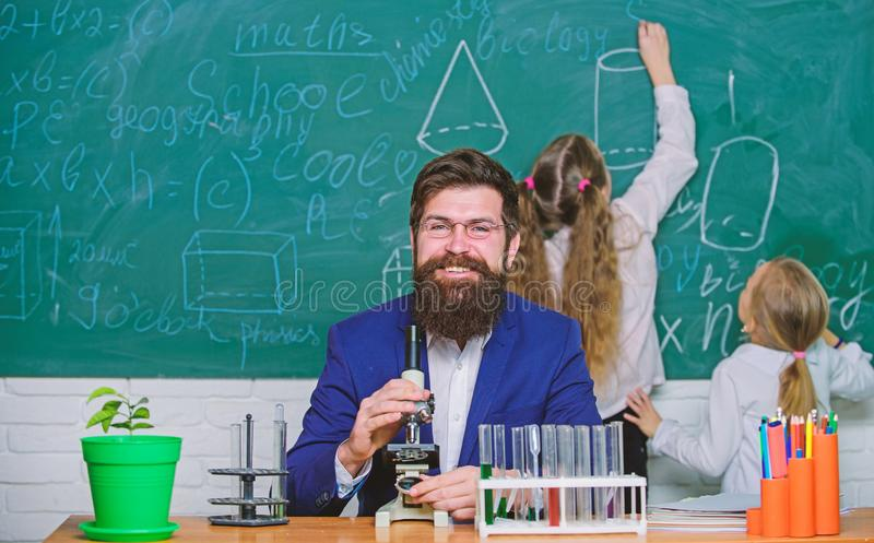 Trabalho farpado do professor do homem com microsc?pio e tubos de ensaio na sala de aula da biologia A biologia joga o papel na c imagem de stock royalty free