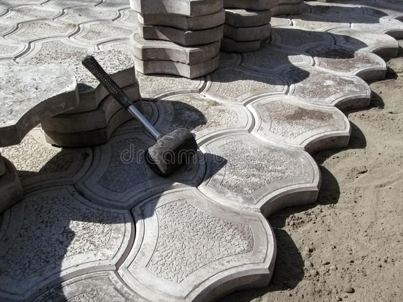 Trabalho inacabado em colocar pavimentos 'biquini ' Um malho inclina-se em uma pilha das telhas e de uma borda desigual dos pavim imagens de stock