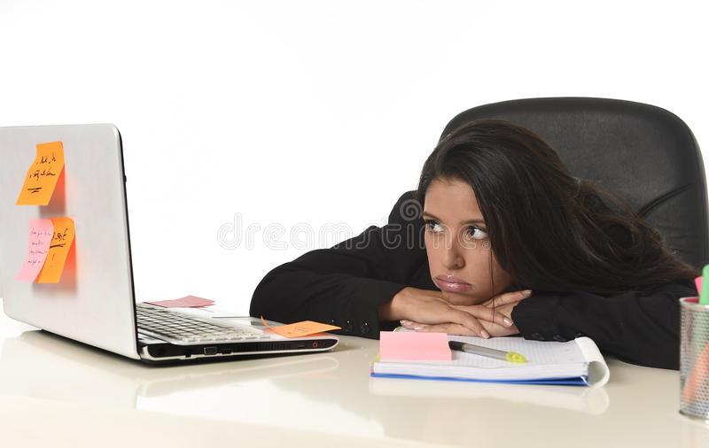Trabalho latin furado da mulher de negócios cansado na mesa do computador de escritório que olha esgotada fotografia de stock royalty free