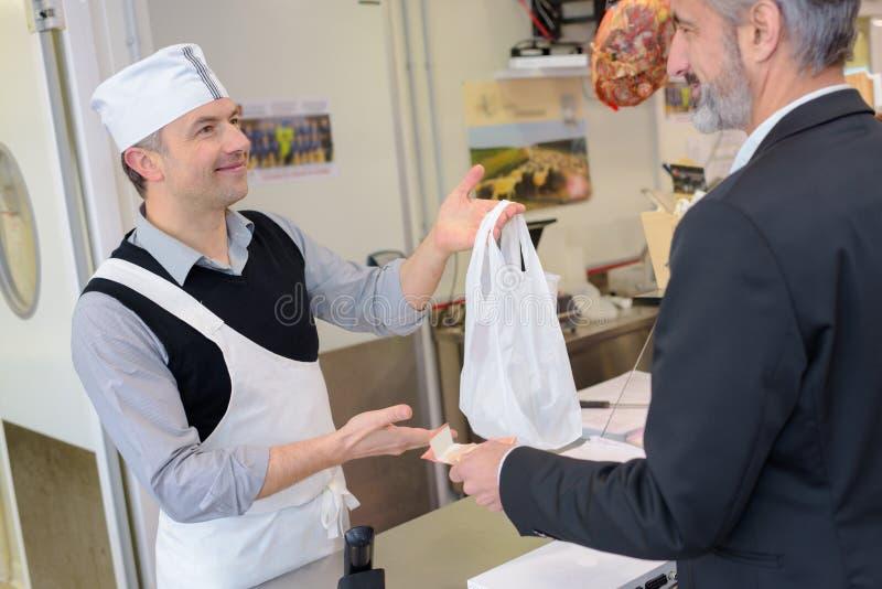 Trabalho na loja de carniceiros - assistente e cliente de loja fotos de stock royalty free