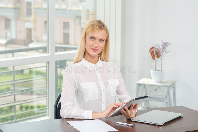 Trabalho na tabuleta A mulher loura trabalha para seus tabuleta e looki fotos de stock royalty free