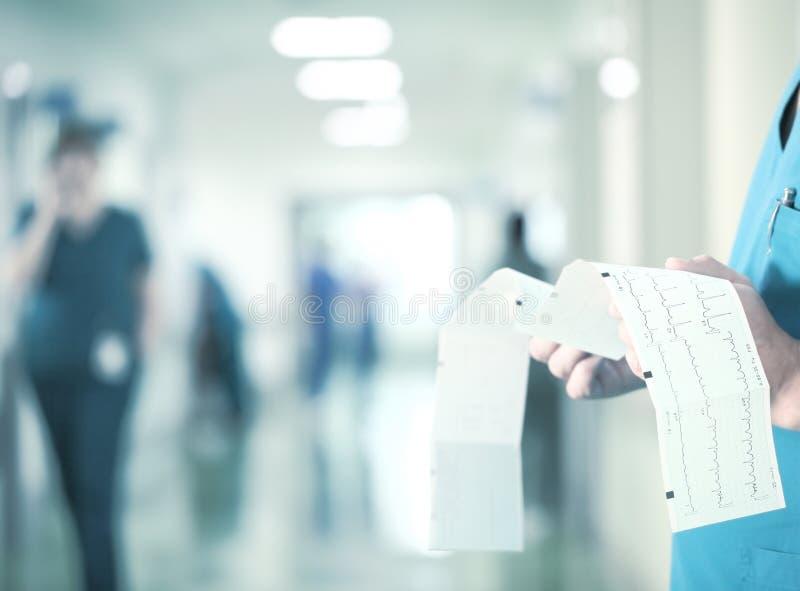 Trabalho no hospital O doutor examina o ECG no fundo fotos de stock