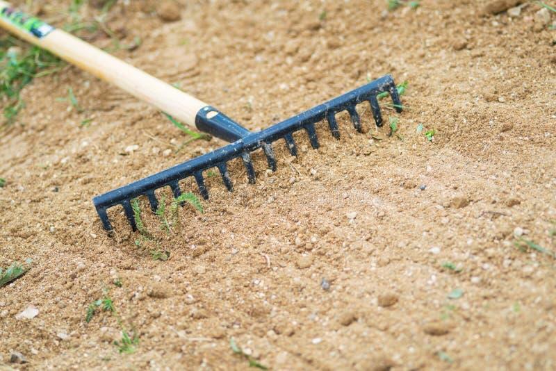 Trabalho no jardim com o ancinho que nivela a terra Trabalho no jardim com ancinho Preparação da terra para semear e plantar imagem de stock