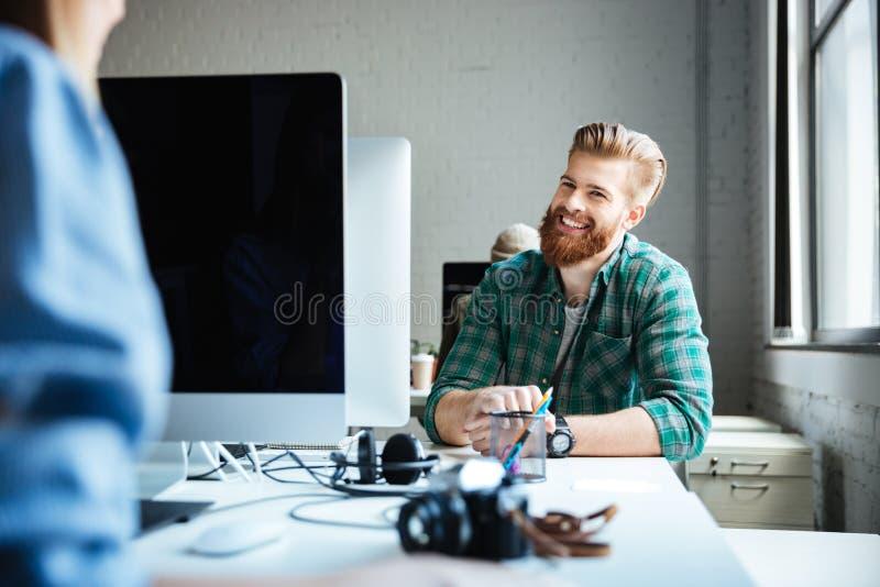 Trabalho novo dos colegas no escritório usando computadores fotos de stock