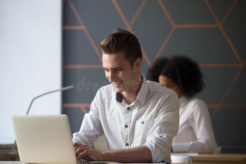 Trabalho ocupado do trabalhador milenar feliz no portátil no escritório fotografia de stock royalty free