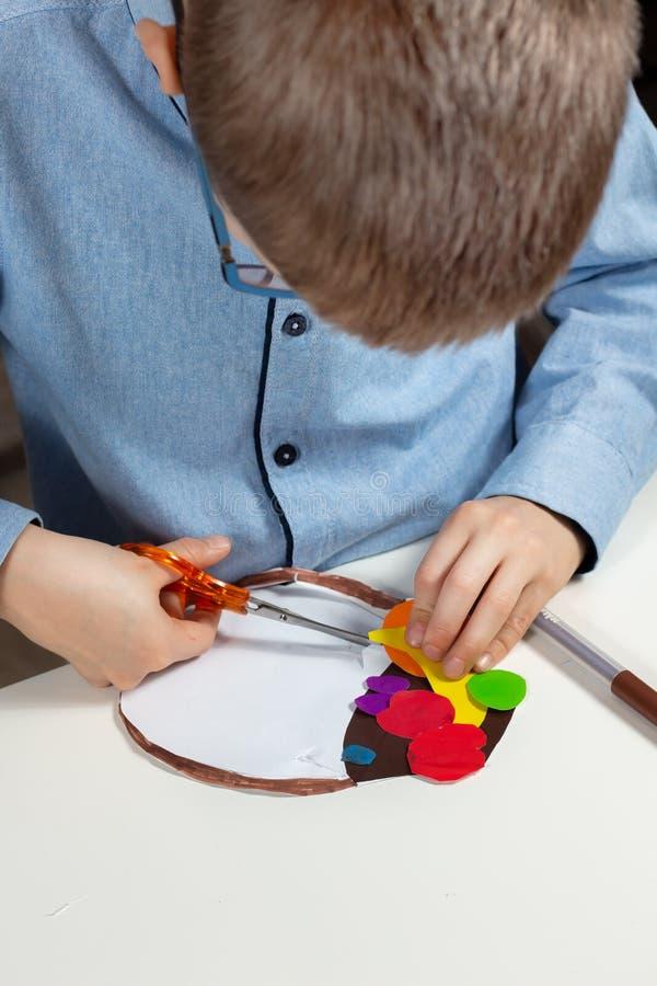 Trabalho plástico feito por uma criança O menino está cortando com tesouras de papel foto de stock royalty free