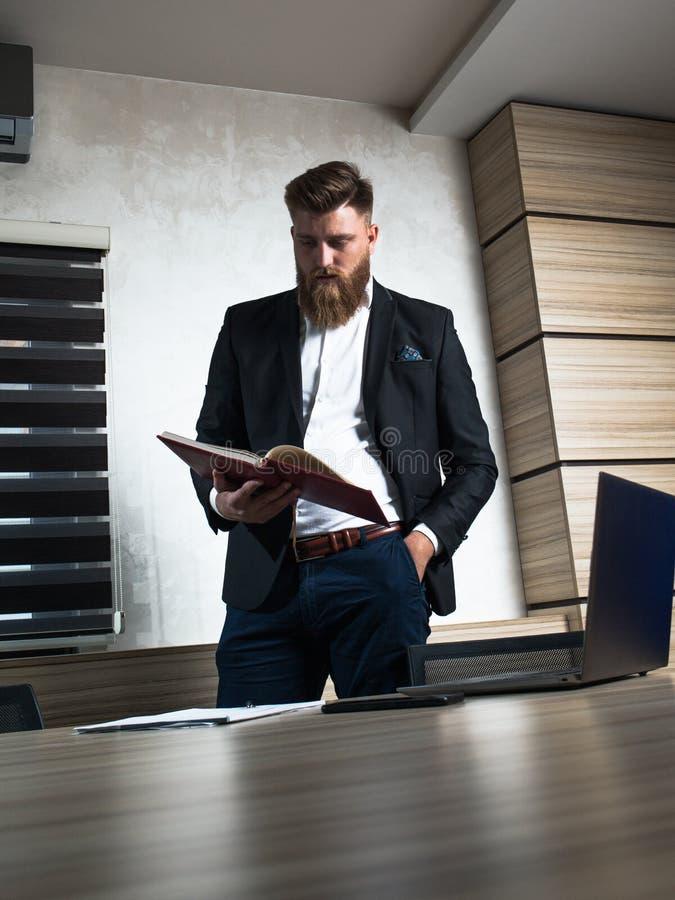 Trabalho tardio do homem de negócios novo da barba no escritório fotografia de stock