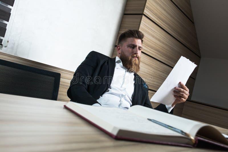 Trabalho tardio do homem de negócios novo da barba no escritório fotos de stock royalty free