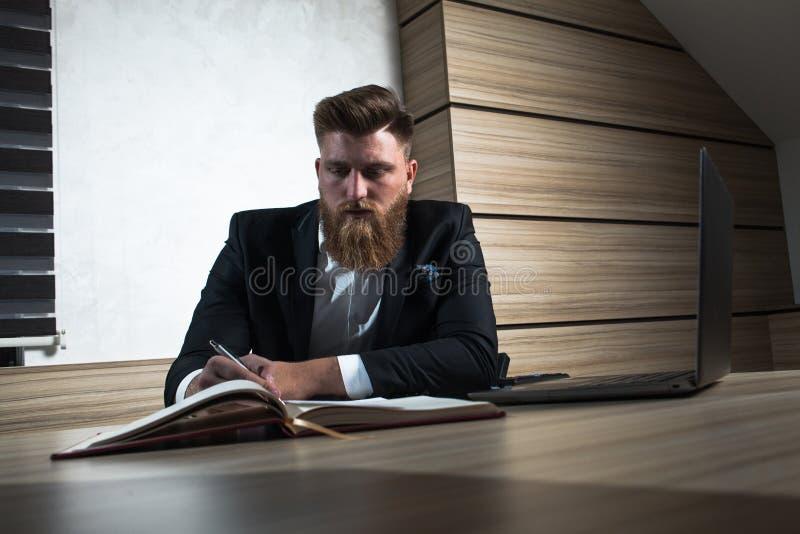 Trabalho tardio do homem de negócios novo da barba no escritório imagens de stock royalty free