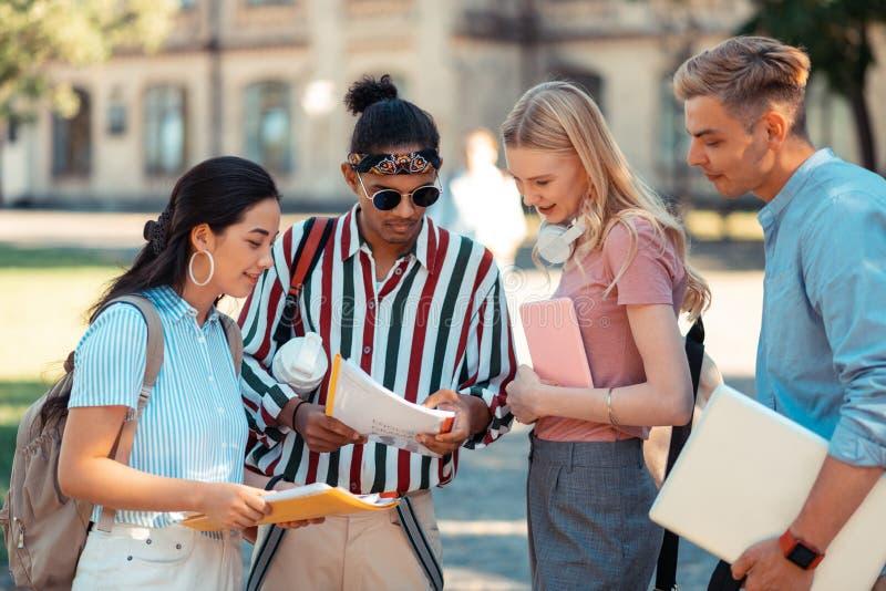 Trabalhos acadêmicos dum semestre da leitura dos estudantes de seus groupmates imagem de stock royalty free