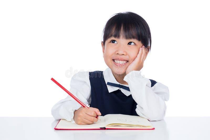 Trabalhos de casa chineses pequenos asiáticos da escrita da menina imagem de stock