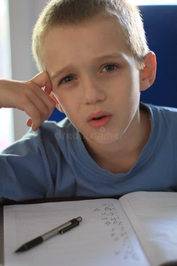 Trabalhos de casa da escrita do menino foto de stock royalty free