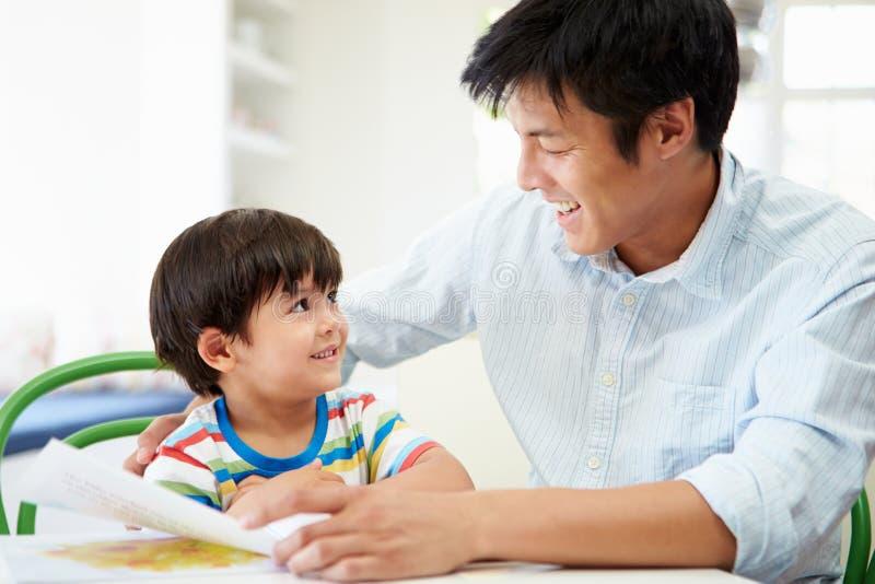 Trabalhos de casa de Helping Son With do pai fotografia de stock royalty free