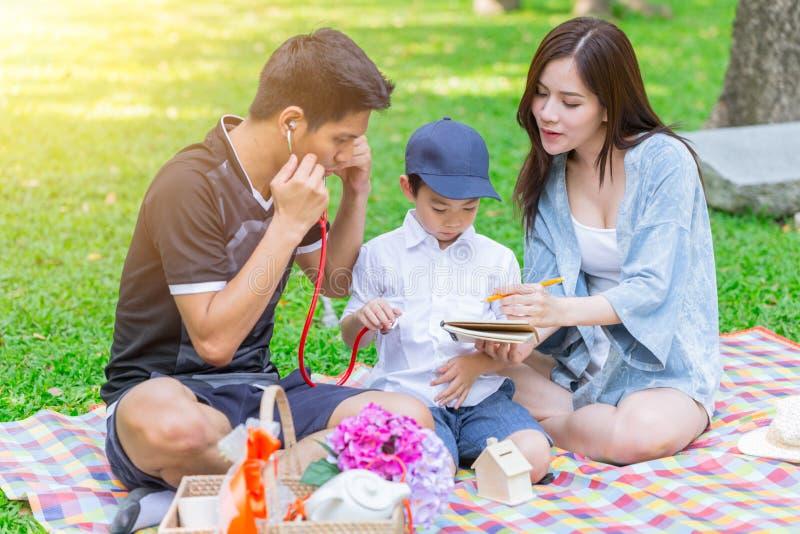 Trabalhos de casa de ensino do filho da família adolescente asiática quando piquenique imagens de stock