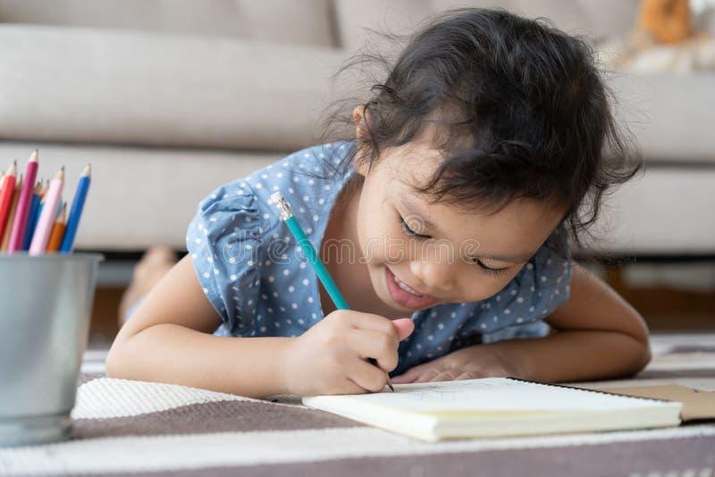 Trabalhos de casa de tiragem e escrita da menina bonito com a pena no papel em sua casa foto de stock royalty free