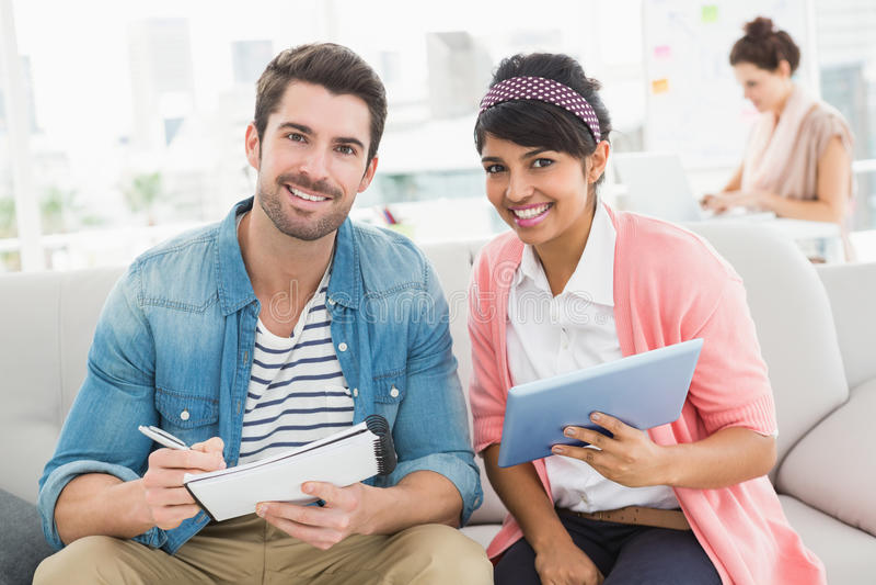 Trabalhos de equipa de sorriso com caderno e tabuleta no sofá imagem de stock