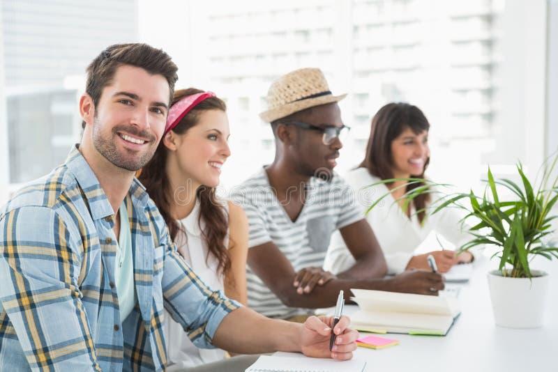 Trabalhos de equipa de sorriso que escutam e que tomam notas imagem de stock royalty free