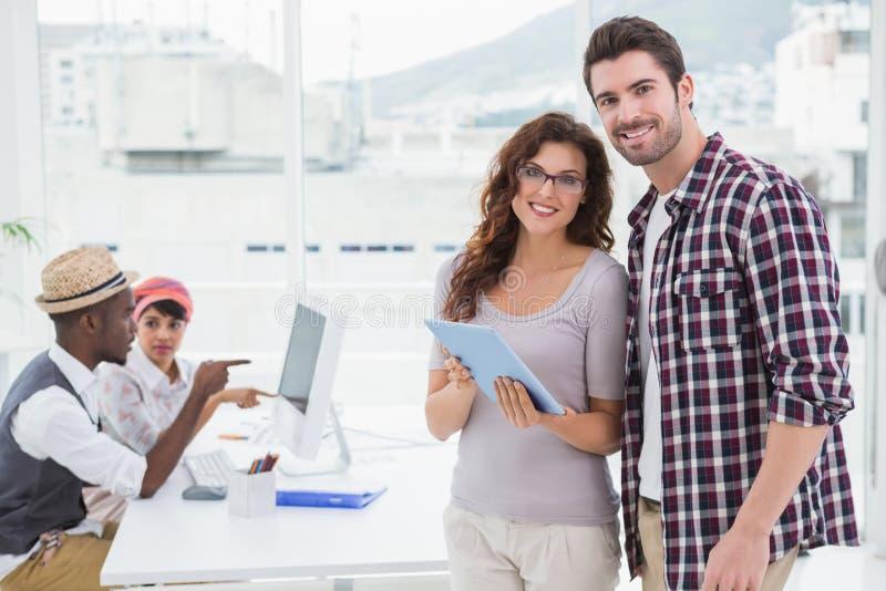 Trabalhos de equipa de sorriso que estão e que usam a tabuleta imagens de stock royalty free