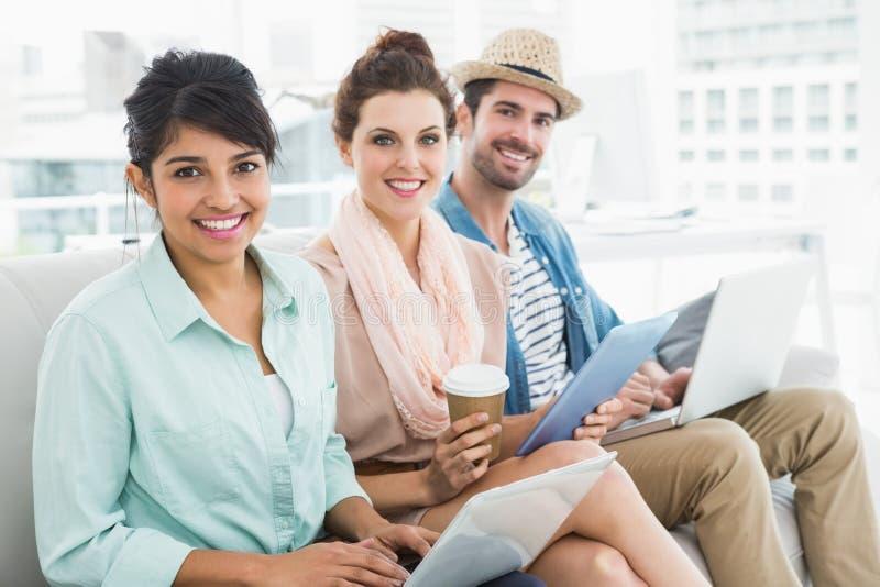 Trabalhos de equipa de sorriso que sentam-se no sofá que olha a câmera fotografia de stock royalty free
