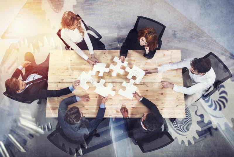 Trabalhos de equipa dos sócios Conceito da integração e da partida com partes do enigma e folha de prova da engrenagem Exposição  fotografia de stock royalty free
